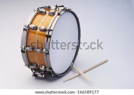 Drum with Drumsticks isolated on white. The Snare drum has a wooden texture and an exclusive inlay.
