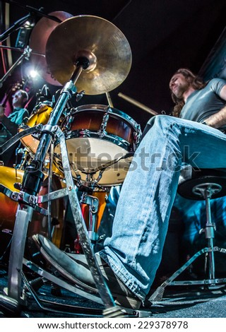 Drummer (focus on the drum and leg) playing on drum set on stage. - stock photo
