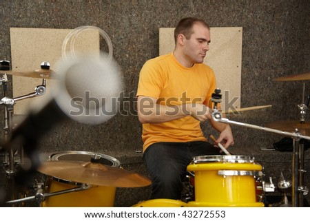drummer near drum kit. microphone in out of focus - stock photo