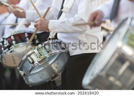 Drummers in a Marching Band. Drummers playing snare drums in parade - stock photo