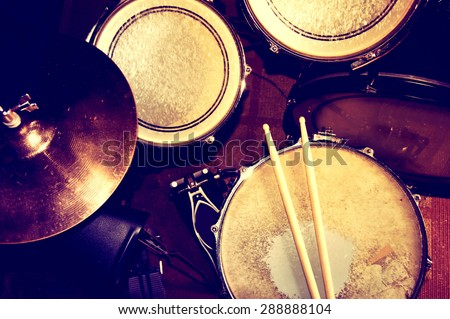 Drums conceptual image. Picture of drums and drumsticks lying on snare drum. Retro vintage instagram picture. - stock photo