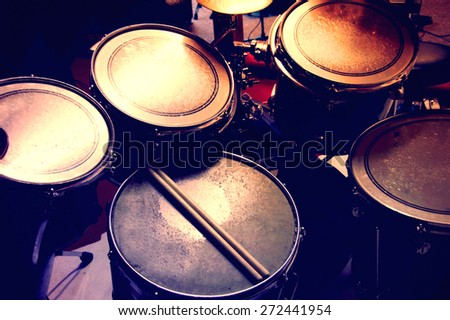 Drums conceptual image. Picture of drums and drumsticks lying on snare drum. Retro vintage picture. - stock photo