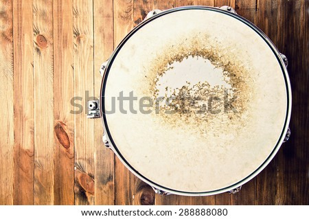 Drums conceptual image. Picture of snare drum lying on wooden background. Retro vintage instagram picture. - stock photo