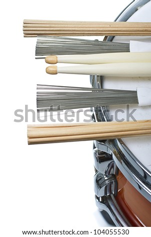 Drumsticks,brushes and unplugged sticks resting on a cherry sunburst colored snare drum, shown only a part of its side and top with the metal rim- isolated on white - stock photo