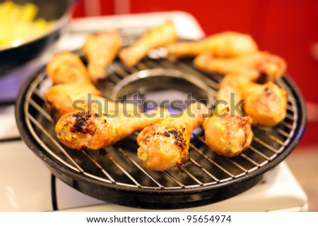 Drumsticks on a grill on gas stove - stock photo