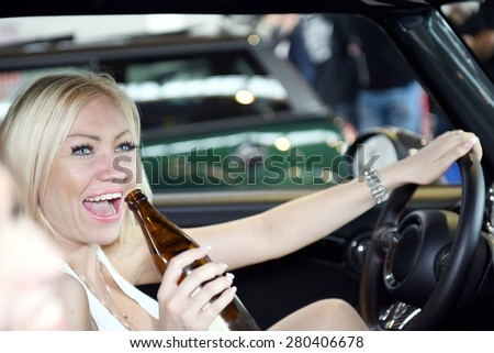 Drunk and happy blonde woman drinking Beer before drive a car. Fun and sensual female driving car with beer bottle in her hand. Concept of alcohol danger and car driving - stock photo