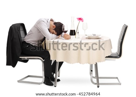 Drunk and lonely guy sitting at a restaurant table with his head down isolated on white background - stock photo