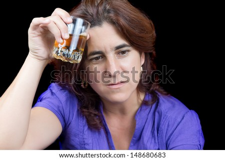 Drunk and sad latin woman holding a glass of liquor isolated on black