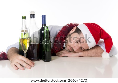 drunk business man in Santa hat with alcohol bottles and champagne glass sleeping after drinking too much at christmas party isolated on a white background - stock photo