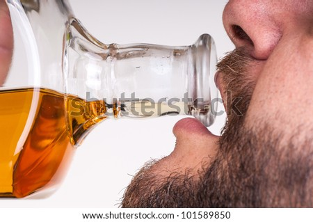 Drunk businessman drinking from a bottle of whisky - stock photo