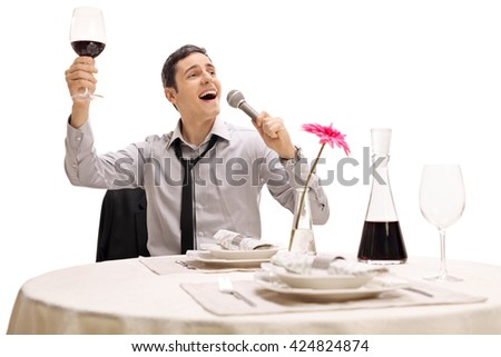 Drunk businessman holding a glass of wine and singing seated at a restaurant table isolated on white background - stock photo