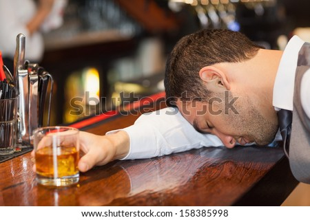 Drunk businessman lying on a counter in a classy bar - stock photo