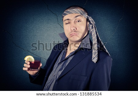 drunk businessman with tie on his head and a glass in her hand - stock photo