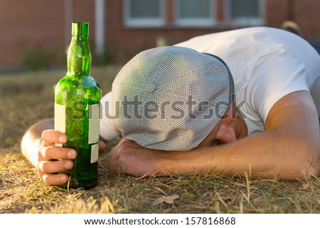 Drunk Caucasian man sleeping on the ground holding a bottle of white wine - stock photo