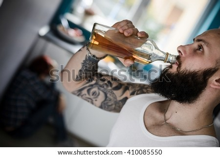 Drunk drinking whisky husband and beaten terrified wife sitting on the floor in the kitchen - stock photo