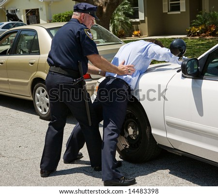 Drunk driver spread eagle on the police car, being patted down. - stock photo