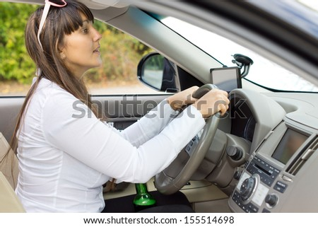 Drunk female driver trying to judge her distances clutching her bottle of booze between her thighs and rising up to peer over the dashboard - stock photo