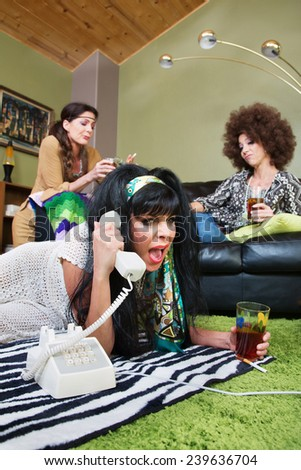 Drunk female with friends yelling into telephone - stock photo
