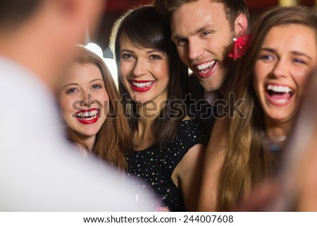 Drunk friends laughing with barman at the nightclub - stock photo