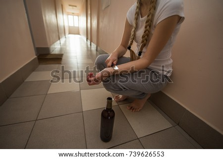 drunk girl blonde with a sharp knife cuts her veins on her hands, beside is an empty bottle. Suicide due to alcohol