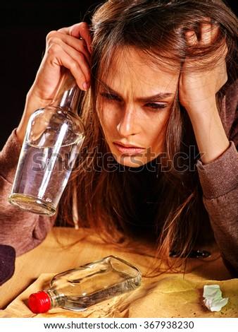 Drunk girl holding bottle of alcohol. Soccial issue alcoholism on black background. - stock photo