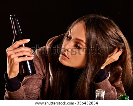 Drunk girl looking at bottle of alcohol. Soccial issue alcoholism. - stock photo