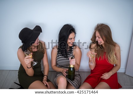 Drunk girls sitting on the floor and drinking a wine. - stock photo