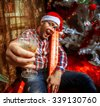 Drunk hipster with glass of champagne under Christmas tree. New year. Christmas mood. - stock photo
