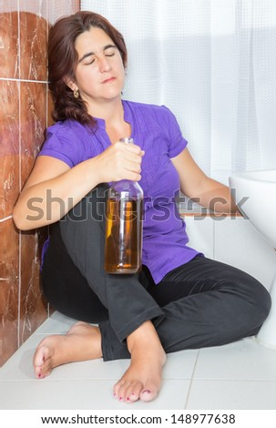 Drunk latin woman sitting on the toilet floor and holding a whisky bottle