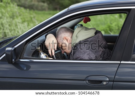 Drunk man asleep at the wheel - stock photo