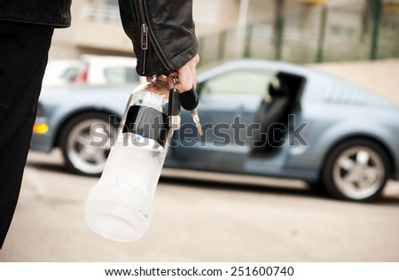 Drunk man driver entering a car with a bottle of alcohol in his hand, his car in the background - stock photo