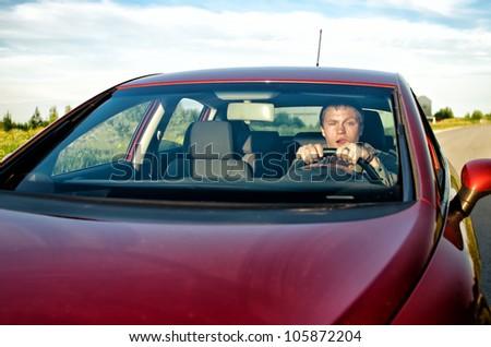 Drunk man driving a car - stock photo