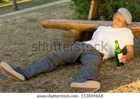 Drunk man fallen asleep on the ground leaning his head on a bench holding a bottle of white wine - stock photo