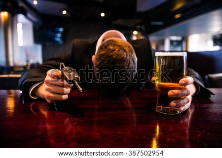 Drunk man holding a beer and car keys in a bar - stock photo