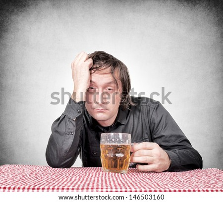 Drunk man holding the pint of beer
