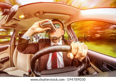 Drunk man in a suit and sunglasses driving on a road in the car vehicle. - stock photo