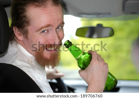 Drunk man in car with a bottle beer - stock photo