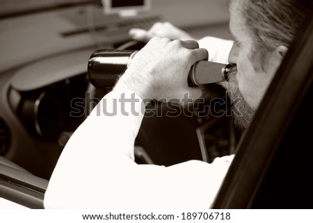 Drunk man in car with a bottle beer in sepia photo - stock photo