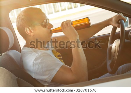 Drunk man is drinking beer in his car - stock photo