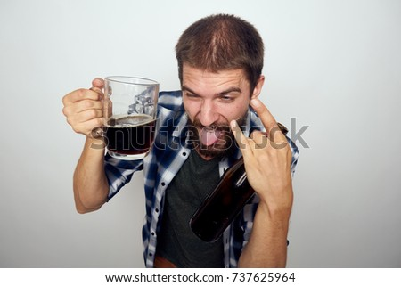 drunk man shows tongue, in his hand a mug of beer, alcohol
