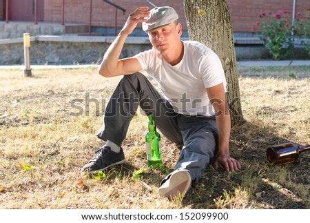 Drunk man sitting at the base of a tree with a bottle of alcohol in front of him and discarded bottles at the side staring morosely ahead of himself