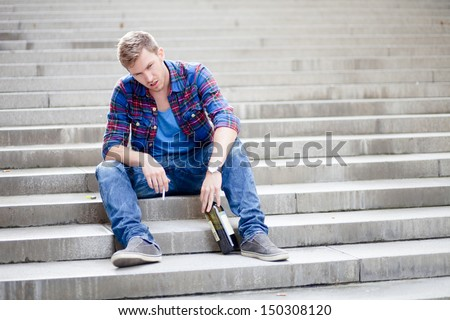 Drunk man sitting on the stairs drinking wine and smoking cigarette - stock photo
