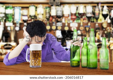 Drunk man sleeping in the bar, with bottle of beer in his hand