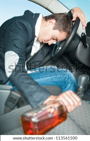 Drunk man sleeps in car with his hand on wheel. Young drunk driver get into accident. Tired person in jeans and gray jacket holding bottle alone in car. Dangerous situation on road. - stock photo