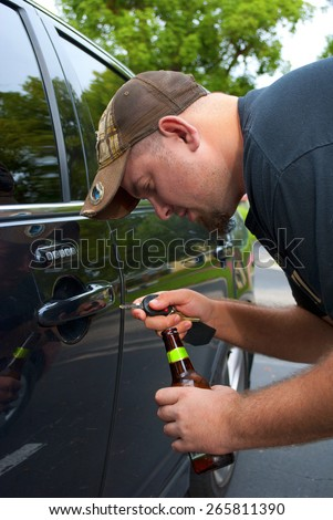 Drunk man struggling to unlock his car so he can drive, which is the wrong thing to do, it is dangerous and illegal. - stock photo