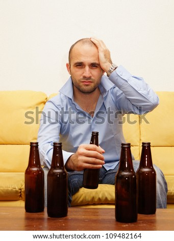 Drunk man with a hangover sitting on the couch - stock photo
