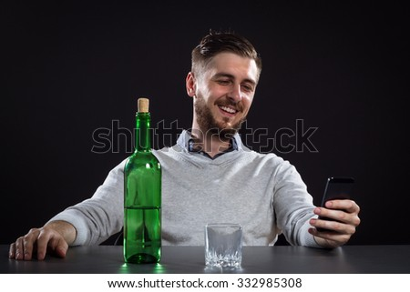 Drunk Man With Bottle Holding Mobile And Going To Make A Call On Black Background - stock photo