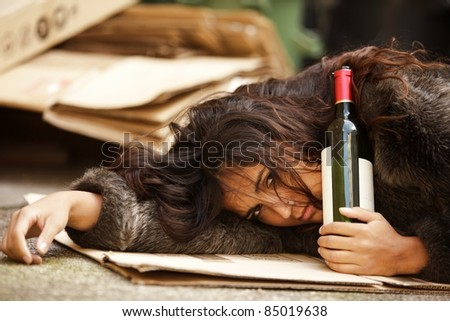 drunk tramp woman holding bottle of wine and lying on pavement - stock photo