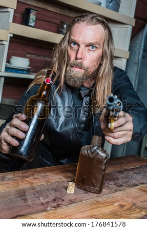 Drunk Western Man Aims Gun Towards You as he Sits at Table - stock photo