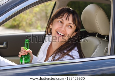 Drunk woman driving laughing out of the side window as she sits behind the steering wheel clutching her bottle of booze - stock photo